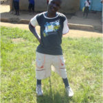 Jeremiah at his school, standing proudly with his new legs