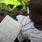 Matumaini girl shows her homework to ELoH volunteer Carolin