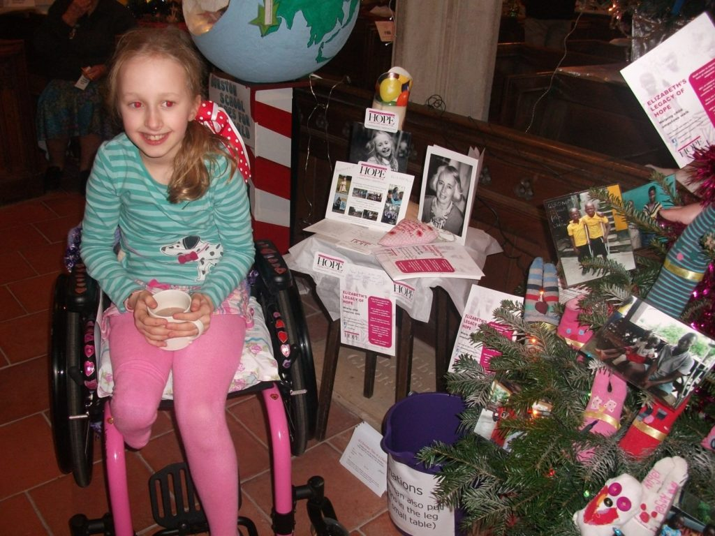 Pollyanna, whose bravery the charity was inspired by, next to the ELoH Christmas Tree